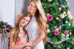 Ευτυχής νέα γυναίκα με τη χαριτωμένη κόρη εφήβων κοντά στα Χριστούγεννα tre Στοκ Εικόνες