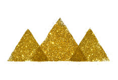 Tre abstrakta trianglar eller pyramider av guld- blänker gnistrandet på vit Arkivfoto