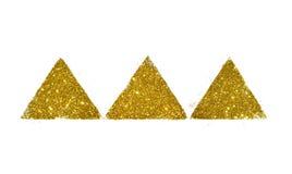 Tre abstrakta trianglar eller pyramider av guld- blänker gnistrandet på vit Arkivfoton