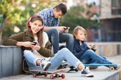 Tre adolescenti con gli smartphones Immagini Stock Libere da Diritti