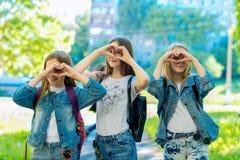 Tre adolescenti Estate in natura Sorriso felicemente In abbigliamento alla moda del denim Il gesto di mani mostra l'amore Concett Fotografia Stock