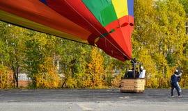 Tre aeronaut förbereder sig att flyga på en ballong från ett sportfält mitt emot bostads- byggnader på en solig dag för höst Arkivfoton