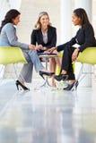 Tre affärskvinnor som omkring möter, bordlägger i modernt kontor Royaltyfria Foton