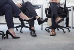 Tre affärspersoner med ben korsade sammanträde på stolar, lågt avsnitt Arkivfoto