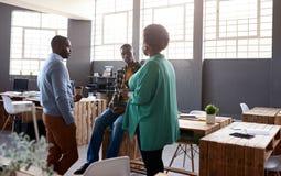 Tre afrikanska arbetskollegor som tillsammans talar i ett modenkontor royaltyfria bilder