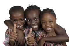 Tre afrikanska ungar som rymmer upp tummar Arkivbild