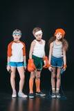 Tre aktiva ungar i sportswearen som poserar med sportutrustning Royaltyfri Foto