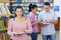 Tre allievi in libreria Immagine Stock