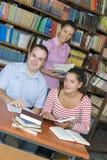Tre allievi in libreria fotografia stock libera da diritti