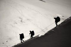Tre alpinisti che camminano attraverso la gamma di alta montagna di Mont Blanc Immagine Stock