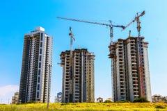 Tre alte costruzioni in costruzione sui precedenti di cielo blu Immagini Stock Libere da Diritti