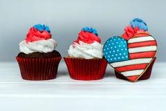 Tre amerikanska patriotiska themed muffin för 4th Juli med hjärta formade amerikanska flaggan grunt djupfält Royaltyfri Foto