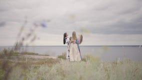 Tre amiche in bei vestiti lunghi da estate con ricamo che fila intorno davanti al fiume Concetto di archivi video