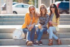 Tre amiche che si siedono sui punti in parco Fotografia Stock Libera da Diritti