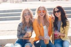 Tre amiche che si siedono sui punti in parco Fotografie Stock Libere da Diritti