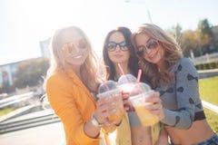 Tre amiche che si siedono sui punti in parco Fotografia Stock