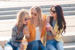 Tre amiche che si siedono sui punti in parco Immagini Stock