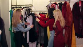 Tre amiche felici allegre stanno esaminando i vestiti in un deposito moderno stock footage