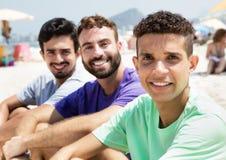 Tre amici alla spiaggia che esamina macchina fotografica Immagine Stock Libera da Diritti