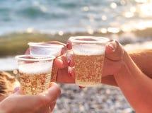 Tre amici alla spiaggia stanno bevendo il vino spumante al tramonto Fotografie Stock