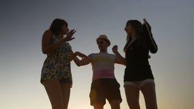 Tre amici che ballano su una spiaggia al tramonto video d archivio