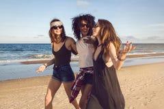 Tre amici che camminano sulla spiaggia e sulla risata Fotografia Stock