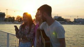 Tre amici che cantano con una chitarra sul ponte sopra il mare su ora legale stock footage
