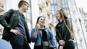 Tre amici che chiacchierano su una pausa caffè durante la pausa, ridente stock footage
