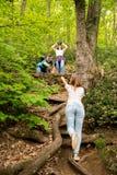Tre amici che fanno un'escursione nella foresta che si aiuta immagine stock libera da diritti