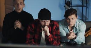 Tre amici che guardano il gioco di sport sulla TV, preoccupantesi per la perdita del gruppo Tipi che si siedono sul sofà a casa  stock footage