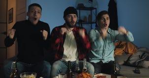 Tre amici che guardano la partita di calcio sulla TV a casa, fan di calcio che si piantano per il loro gruppo video d archivio