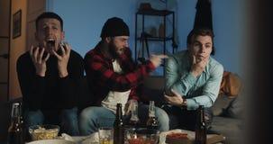 Tre amici che guardano la partita di calcio sulla TV a casa, fan di calcio che si piantano per il loro gruppo E stock footage