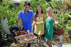 Tre amici che hanno un pranzo del barbecue Fotografia Stock