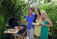 Tre amici che hanno un pranzo del barbecue Immagini Stock
