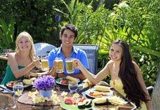 Tre amici che hanno un pranzo del barbecue Fotografie Stock