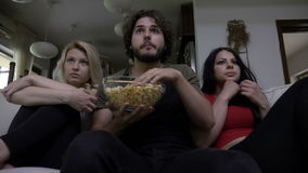 Tre amici che mangiano il popcorn guardano insieme il film horror e molto sono spaventati archivi video