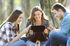 Tre amici che per mezzo dei dispositivi multipli fotografie stock libere da diritti