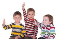 Tre amici che tengono i pollici in su Fotografia Stock