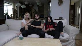Tre amici combattono sopra il telecomando a casa nel salone e cambiano i canali televisivi video d archivio