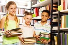 Tre amici con i libri che stanno scaffale per libri vicino Immagine Stock Libera da Diritti