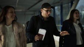 Tre amici con la valigia e documenti che camminano nel corridoio alla reception video d archivio