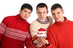 Tre amici danno la casella con il regalo fotografia stock