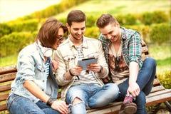 Tre amici dei giovani che per mezzo della compressa Fotografia Stock