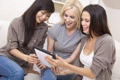 Tre amici delle donne che per mezzo del calcolatore del ridurre in pani Fotografia Stock
