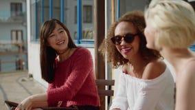 Tre amici delle donne che si incontrano al caffè all'aperto stock footage