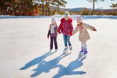 Tre amici di bambina imparano pattinare Ricreazione e feste all'aperto fotografie stock libere da diritti