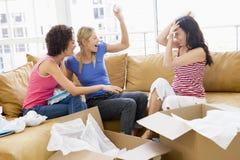 Tre amici di ragazza che disimballano le caselle nella nuova casa Fotografia Stock Libera da Diritti