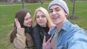 Tre amici, fanno il selfie per una passeggiata nel parco Bionda, castana e un giovane Diverta e goda della vita video d archivio