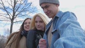 Tre amici, fanno il selfie per una passeggiata nel parco Bionda, castana e un giovane Diverta e goda della vita archivi video