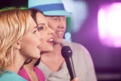 Tre amici felici che cantano in microfoni immagine stock libera da diritti